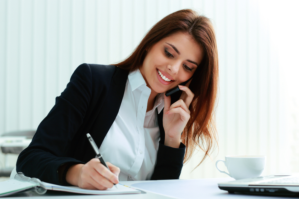 Buyer Persona Interviews | Businesswoman talking on the phone and writing notes