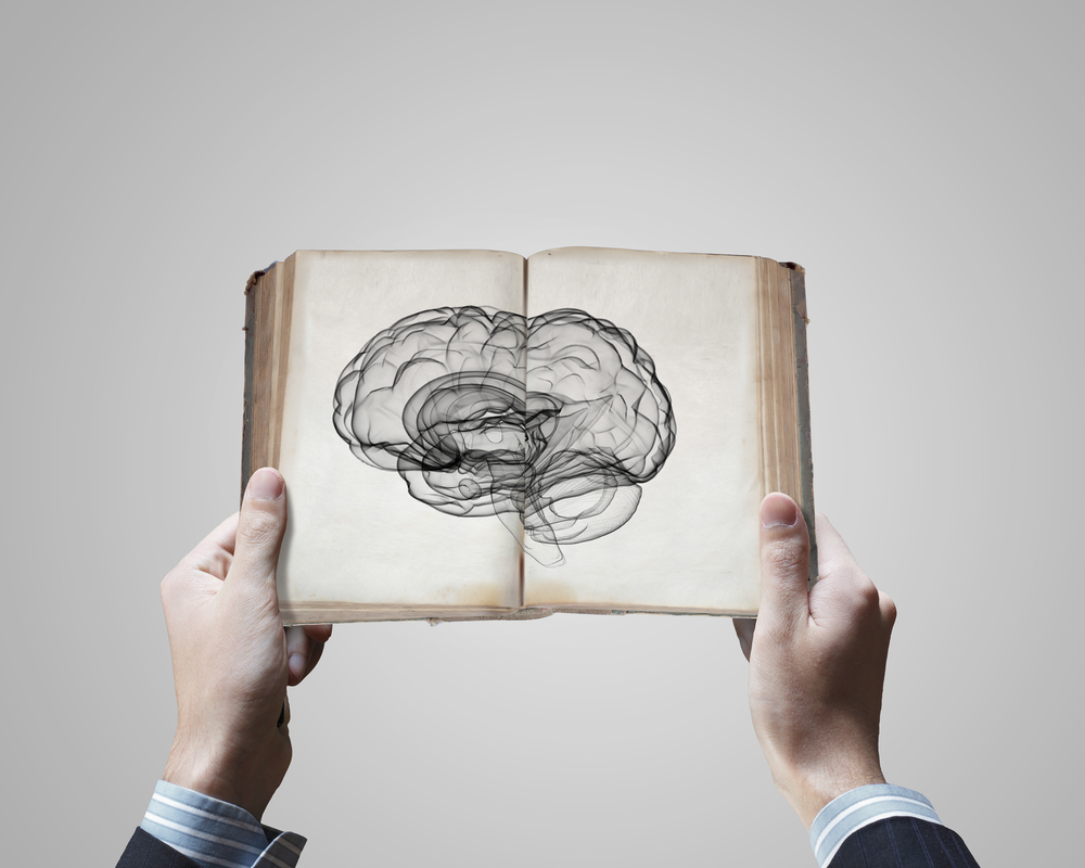 SEO for beginners | SEO glossary | man holding book with brain sketch