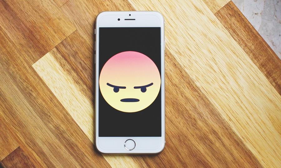 Bad reviews - angry Facebook emoji on phone